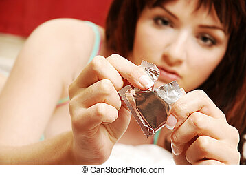 Woman opening condom - A beautiful young woman opening a...