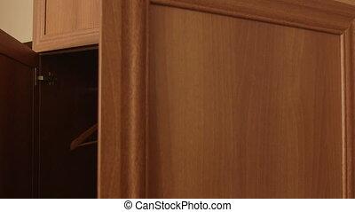 Woman opening door of empty wardrobe hanging clothes on hangers