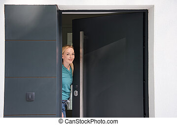 woman opening her house door - young beautiful woman opening...