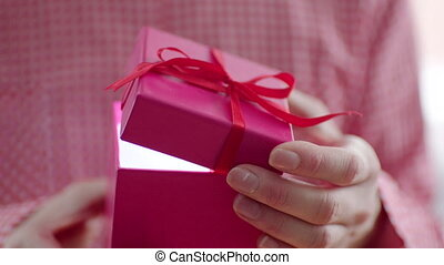 Woman opening holiday gift with red ribbon and light inside