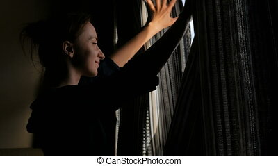 Woman opening window curtains - Happy woman opening curtains...