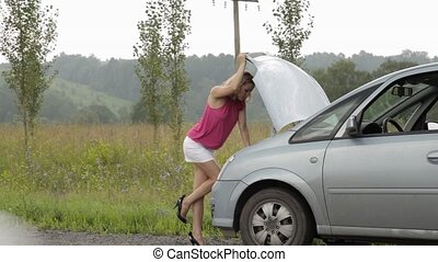 woman opens a hood of her broken car. girl in a short skirt...