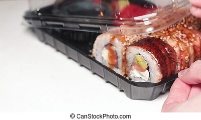 Woman opens a plastic container with fresh Japanese sushi.
