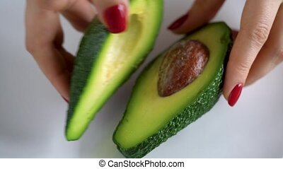 Woman opens avocado. The concept of modern healthy eating - ...