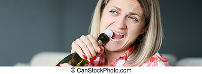 Woman opens bottle of champagne with her teeth.