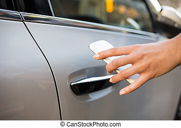 Woman opens her car with her mobile phone