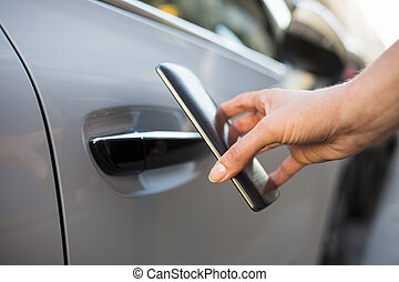 Woman opens her car with her smart phone