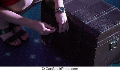 Woman opens padlock on old box