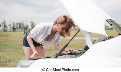 woman opens the hood Broken car. girl looks at a damaged engine.
