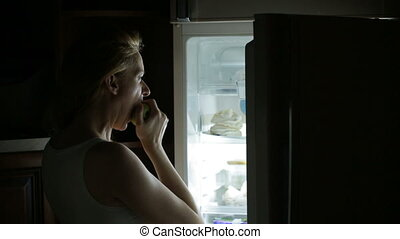 Woman opens the refrigerator at night. bulimia, sandwich, pastry