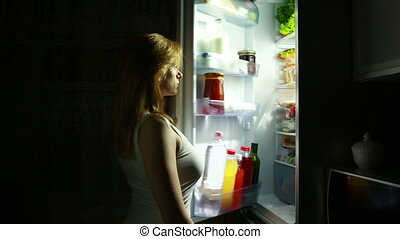 Woman opens the refrigerator at night. night hunger. diet. eating cake