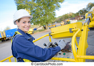 Woman operating controls of cherry picker bucket