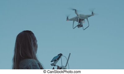 Woman operating drone with remote controller and recording...
