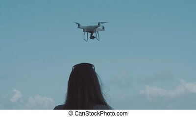 Woman operating drone with remote controller - Back view of...