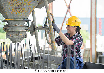 woman operator pouring mixture in the cement moulding