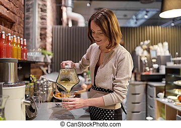 woman or barmaid cooking smoothie at vegan cafe - small...