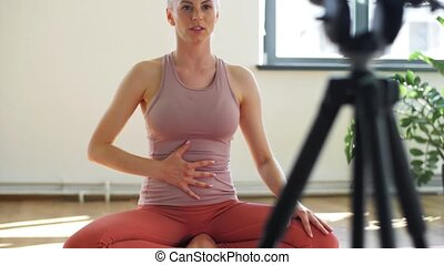 fitness, sport and video blogging concept - woman or blogger with camera on tripod recording online yoga class in gym or studio