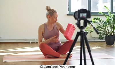 fitness, sport and video blogging concept - woman or blogger with camera on tripod and exercise block recording online yoga class in gym or studio