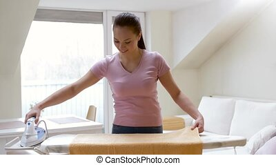 woman or housewife ironing towel by iron at home - housework...