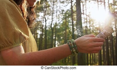 occult science and supernatural concept - young woman or witch with smoking white sage performing magic ritual in forest