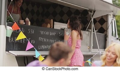 woman ordering at food truck menu for friends - street sale,...
