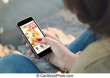 woman ordering fast food with her smartphone and touching the screen. All screen graphics are made up.