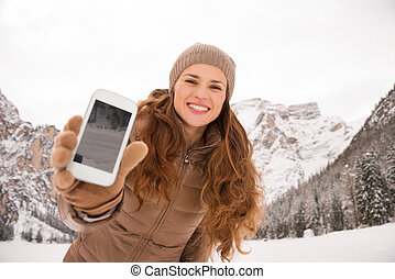 Woman outdoors among snow-capped mountains showing cell...