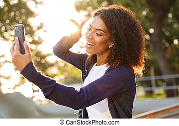 Woman outdoors in park using mobile phone make selfie with peace gesture.