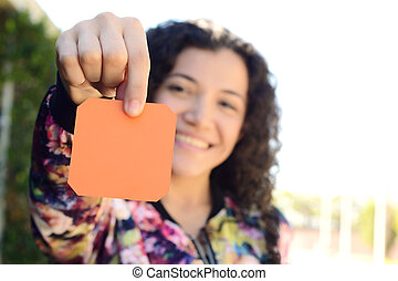 Woman outdoors showing a blank notepad.