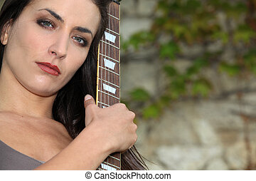 Woman outdoors with guitar