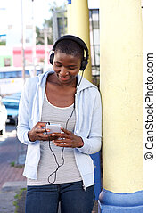 Woman outside leaning on column with phone and headphones