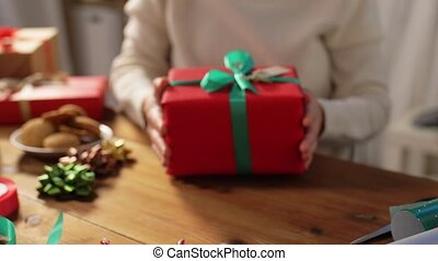 woman packing christmas gifts at home - holidays, new year ...