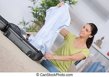 woman packing clothes into travel bag