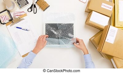 woman packing frame to bubble wrap at post office -...