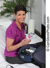 Woman packing her vanity bag
