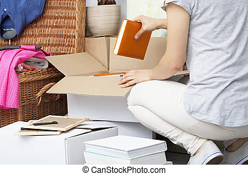 Woman packing house stuff into white boxes