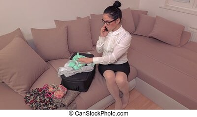 Woman packing luggage and talking on smartphone
