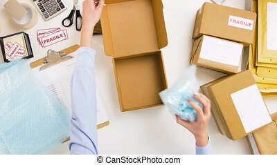 woman packing mug to parcel box at post office - delivery,...