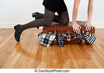 Woman packing overfilled suitcase - Woman standing on her...