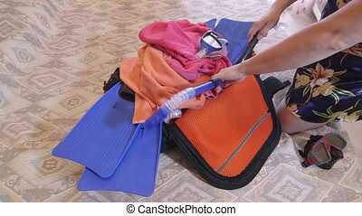 Woman packing overfilled travel bag for summer getaways