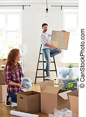 Woman packing stuff and man with painting on ladder in blurred background moving out from home