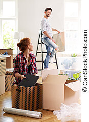 Woman packing stuff into boxes while moving out with husband to other house
