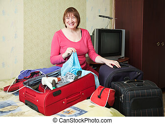 Woman packing Suitcase at home