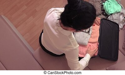 Woman packing suitcase on bed at home top view