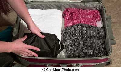 Woman packing suitcase on bed for summer vacation