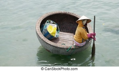 Woman paddling a traditional Vietnamese round boat on Nha Trang Bay.