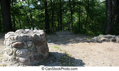 Young sexy woman in shorts climb stairs hill in Verkiai park. Pass near old stone pagan altar.