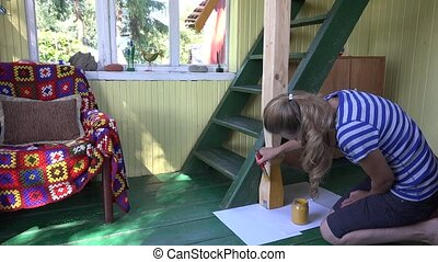 woman paint wooden column with yellow colour in country home. 4K