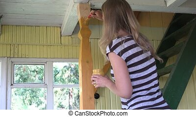 woman paint wooden column yellow paint to ceiling in room. 4K