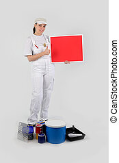 woman painter holding red panel for message